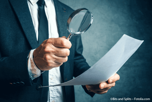Tax inspector investigating financial documents through magnify